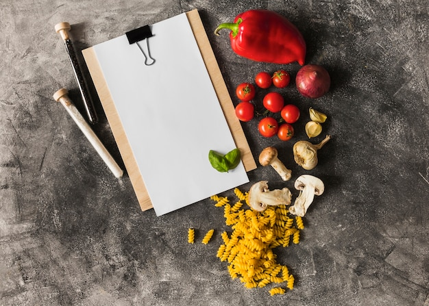 Raw fusilli with ingredients and paper on clipboard against grunge background