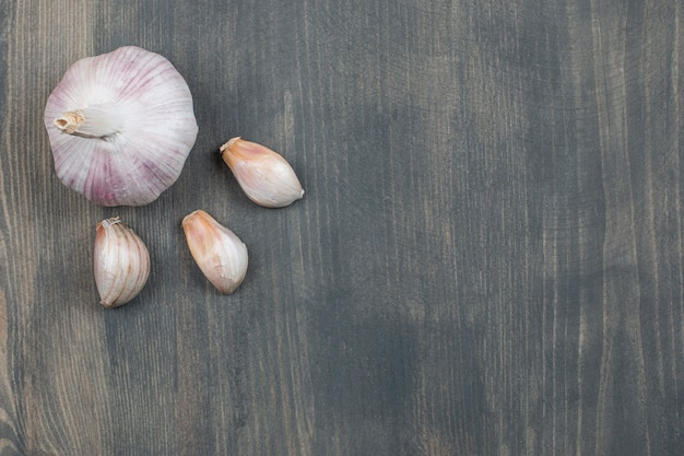 Raw garlic with segments isolated on a wooden table