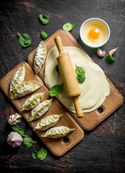Raw gedza dumpling. a homemade dumplings gedza with meat on dark rustic table