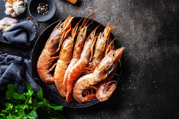 Raw giant shrimps on dark table