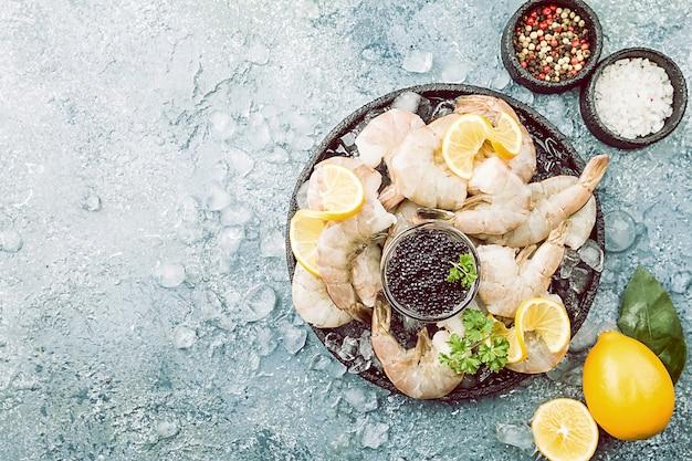 Сырые гигантские креветки с лимоном и специями на сковороде над серым