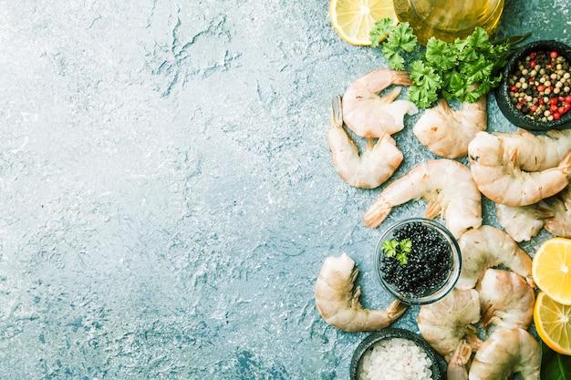 Сырые гигантские креветки с лимоном и специями на сером