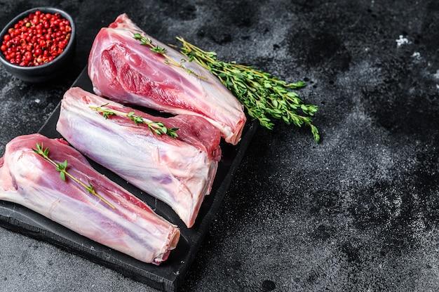 生の山羊は大理石の板の上で肉をすね肉にします。黒いテーブル。上面図。スペースをコピーします。