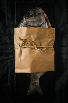 Raw  Golden fish in paper