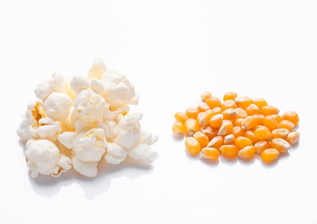 Raw golden sweet corn and popcorn seeds on white background