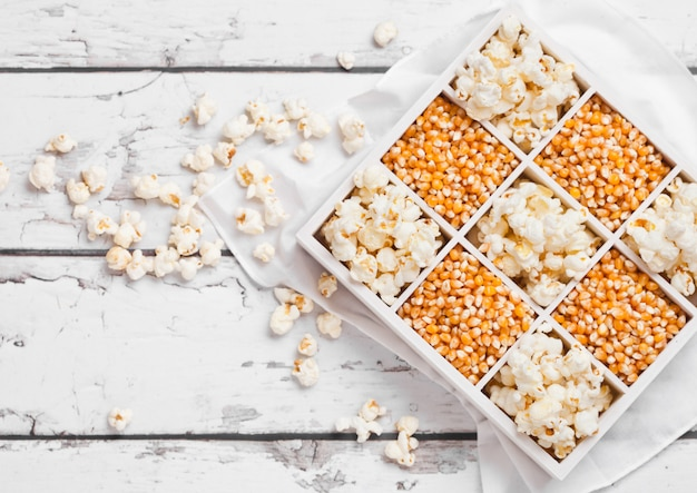 Raw golden sweet corn seeds and popcorn in white wooden box on light background.top view