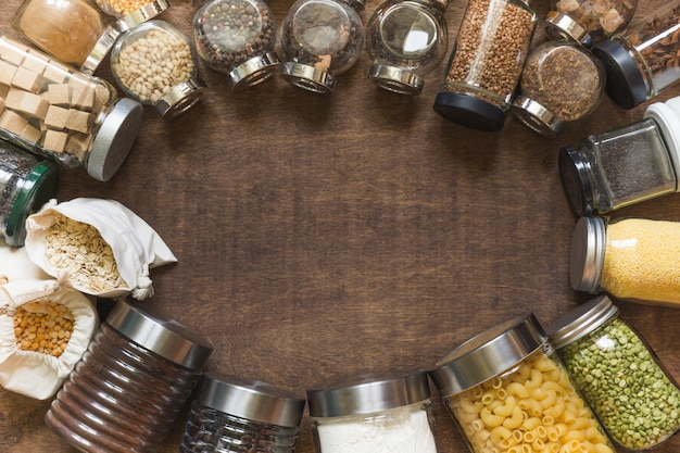 Raw grains, cereals and pasta in glass jars on wooden table background