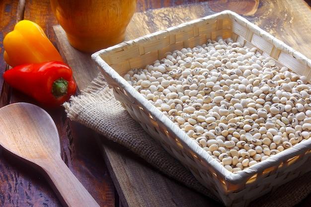 Сырые зерна фасоли фрадиньо в деревенской корзине на деревянном столе. вид сверху