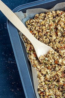Raw granola, muesli from oat flakes, varius of nuts, honey, pumpkin seeds on baking sheet. home cooking
