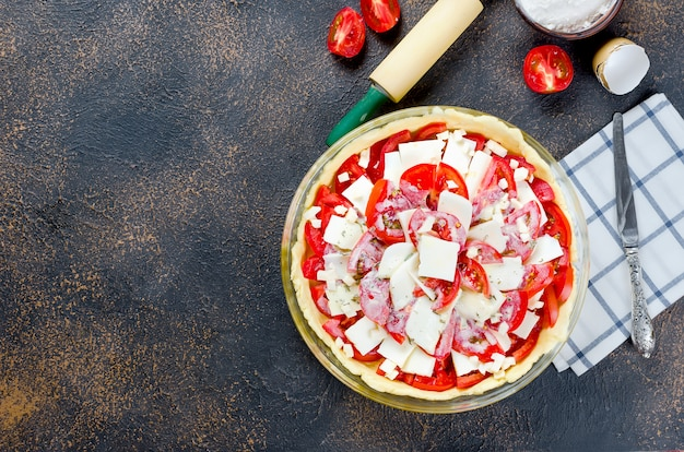 Raw greek pie with feta and tomatoes for baking