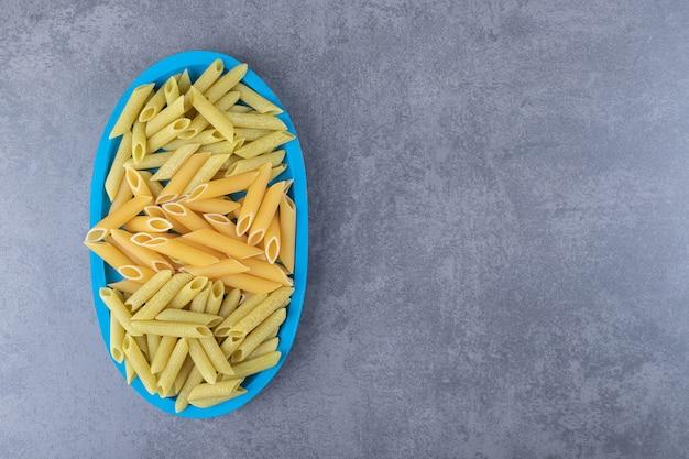 青いプレートに生の緑と黄色のペンネパスタ。