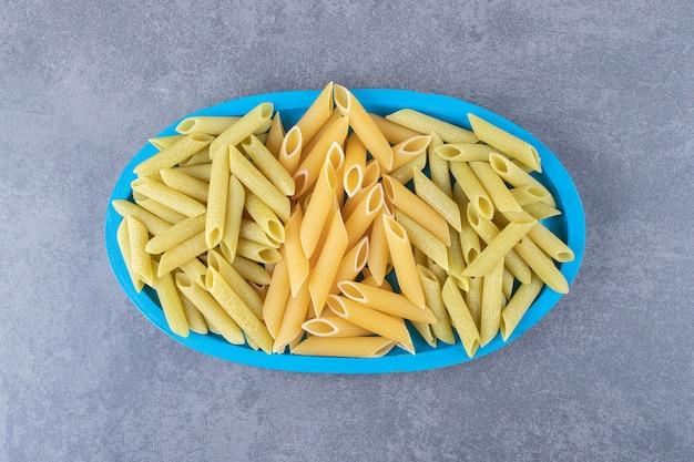 Сырые зеленые и желтые макаронные изделия пенне на синей тарелке.
