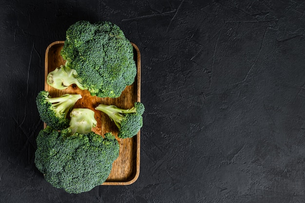 Raw green broccoli on a wooden bowl