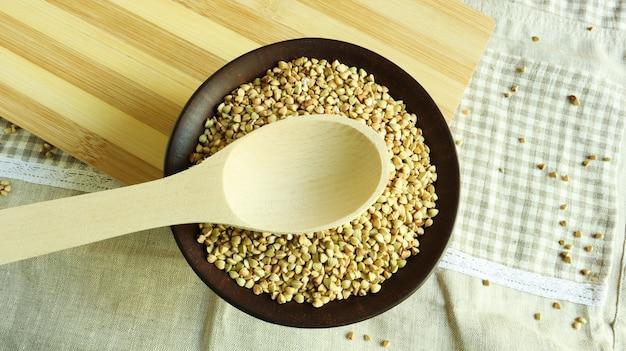 茶色の粘土板と木のスプーンで生のそば。ビーガンオーガニックフードのコンセプトです。