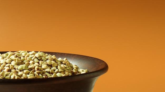 Сырая зеленая гречка в коричневой глиняной тарелке на коричневом фоне. концепция веганских органических продуктов питания. понятие о диете, похудании, здоровом и правильном питании. скопируйте место для текста или логотипа.