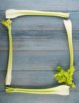 木の背景の上面図に生の緑のセロリの茎。コピースペースと古い木製の素朴なテーブルの上の新鮮な有機正方形野菜フレーム