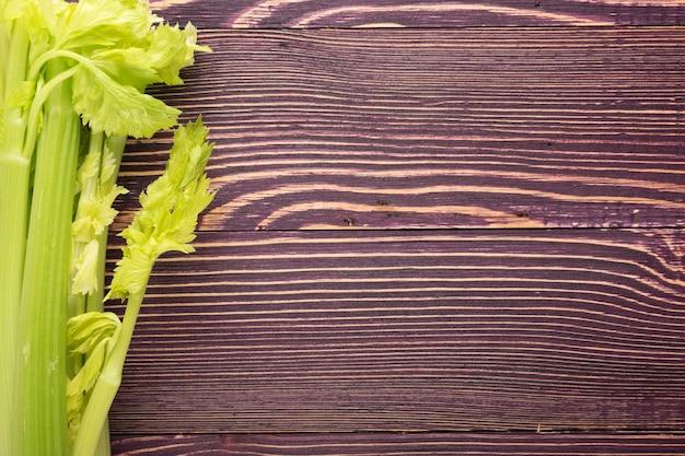 木の背景の上面図に生の緑のセロリの茎。古い木製の素朴なテーブルの上の新鮮な有機野菜
