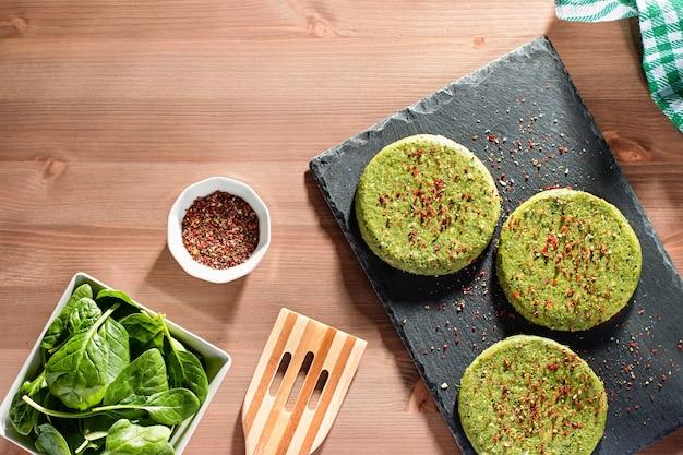 Сырые зеленые куриные и шпинатные гамбургеры со специями на каменной тарелке при жестком свете, вид сверху. макет здорового питания, копия пространства