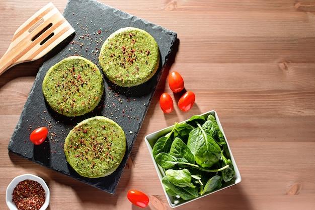 生のグリーンチキンとほうれん草のハンバーガーとスパイスをハードライトで石のプレートに載せた上面図。健康的な食事のレイアウト、コピースペース