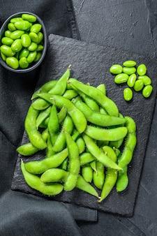 生グリーン枝豆。黒の背景。上面図