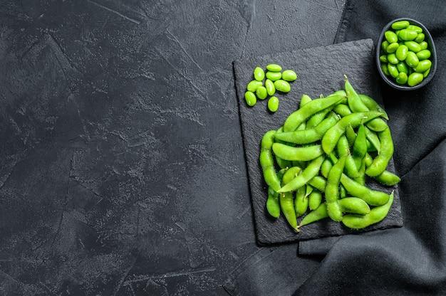 黒の背景に生の枝豆大豆