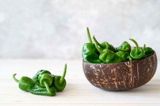 Сырой зеленый острый мексиканский перец халапеньо, испанский перец падрон на белом столе