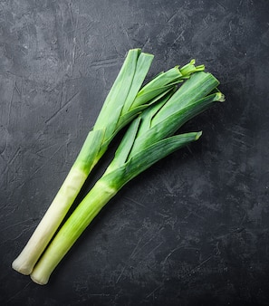Сырой зеленый органический лук-порей на черном