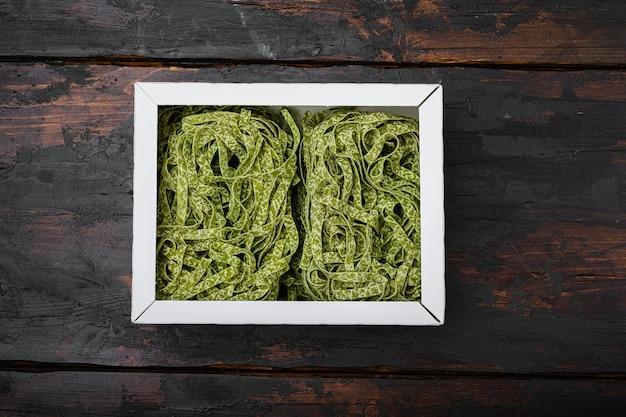 원시 녹색 파스타 팩 세트, 오래된 짙은 나무 테이블 배경 위에 있는 평면도