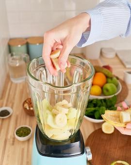 채식주의 수직 아침 식사를 준비하는 원시 녹색 스무디 음료 여자