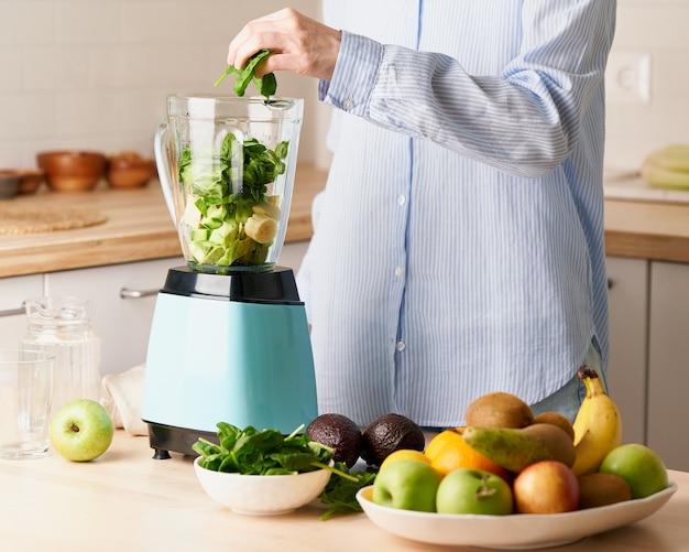 채식주의 아침 식사를 준비하는 원시 녹색 스무디 음료 여자