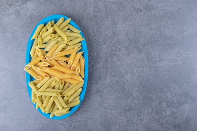 Raw green and yellow penne pasta on blue plate.