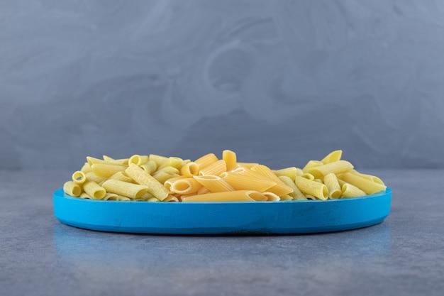 Pasta di penne verde e gialla cruda sul piatto blu.