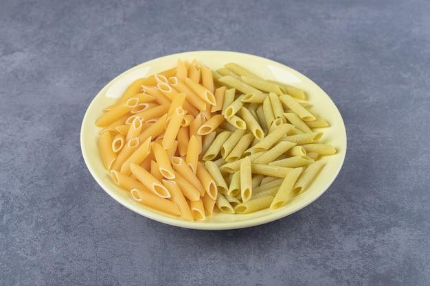 Pasta di penne verde e gialla cruda sul piatto giallo.