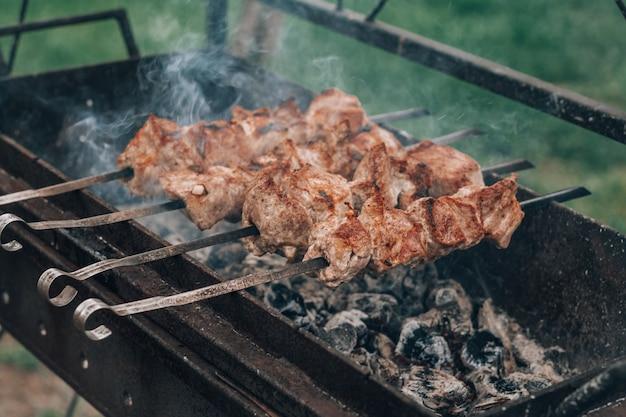 Сырое мясо гриль на шпажках готовится на углях, готовим шашлык на открытом воздухе