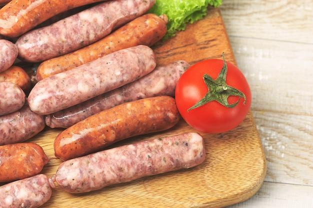 Сырые колбаски гриль на деревянной круглой доске с помидорами