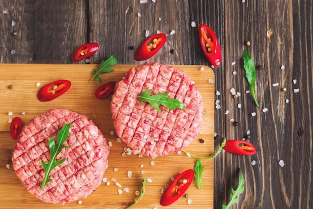 Бургеры из сырого говяжьего фарша с перцем чили и рукколой на деревенском деревянном столе. вид сверху.