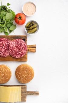 生の牛ひき肉バーガーステーキのカツレツとパンがセットされた調味料、白い石の背景、上面図フラットレイ、テキスト用のコピースペース