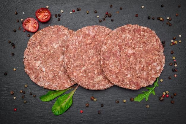 暗い大理石の背景に生牛ひき肉バーガーステーキカツレツ。
