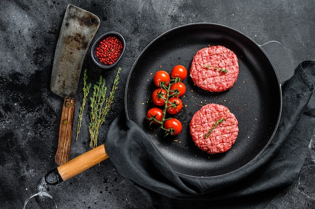 Raw ground beef meat burger steak cutlets in a pan.