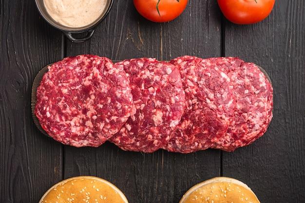 검은 나무 테이블에 원시 갈은 쇠고기 고기 버거 스테이크 커틀릿 세트, 평면도 평면 누워