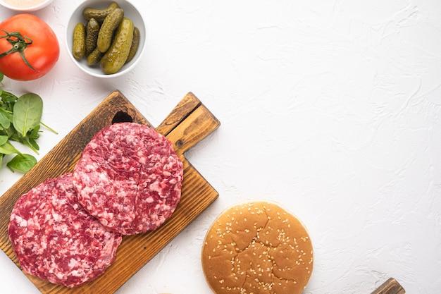 원시 갈은 쇠고기 고기 버거 스테이크 커틀릿 세트, 흰색 돌 테이블, 평면도 평면 누워