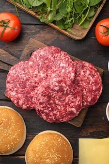 古い暗い木製のテーブルの背景に、材料とパンがセットされた生の牛ひき肉のハンバーガーステーキのカツレツ、上面図フラットレイ