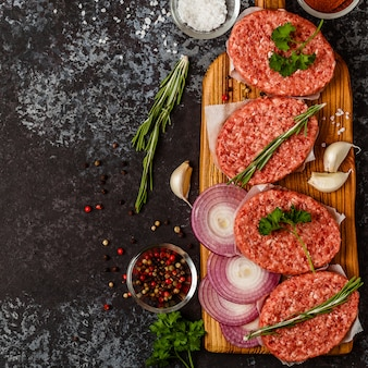 Raw ground beef meat steak cutlets with herbs and spices.