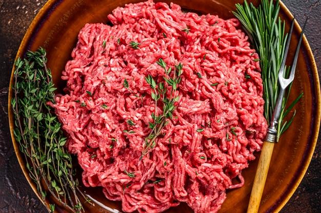Сырой говяжий фарш или телятина на деревенской тарелке с зеленью