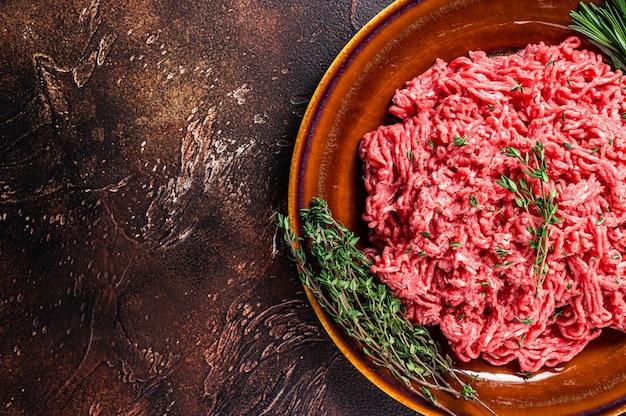 허브와 함께 소박한 접시에 원시 갈은 쇠고기 또는 송아지 고기.