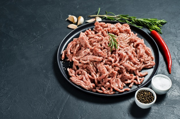 Raw ground beef on a stone board. ingredients for cooking, rosemary, chili pepper, garlic, salt.