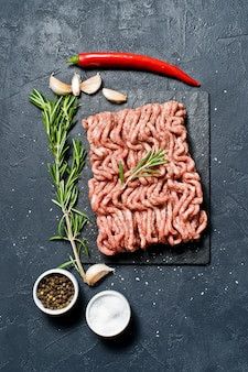 Raw ground beef on a stone board.