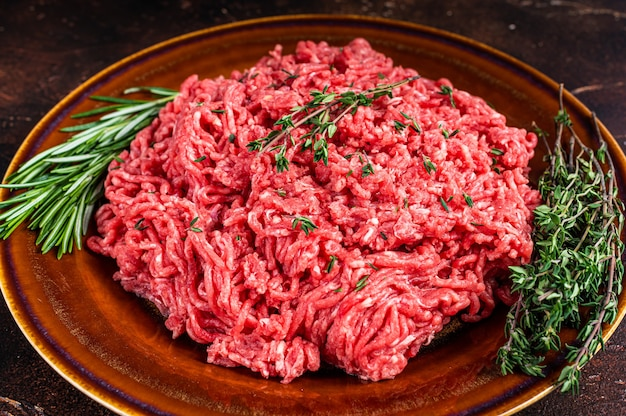 Raw ground beef or veal meat on a rustic plate with herbs. dark background. top view.