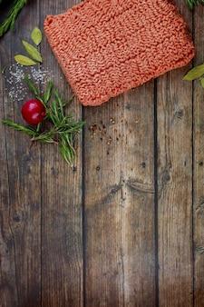 Сырой говяжий фарш со специями и розмарином на деревянных фоне.