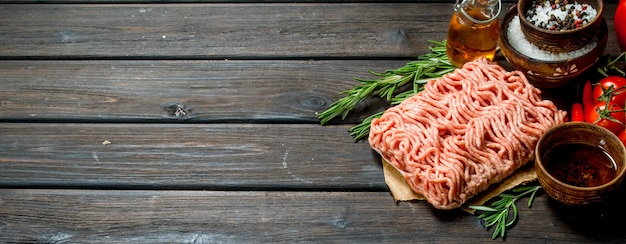 Raw ground beef with tomatoes and spices. on a wooden background.